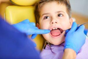 A little boy having his teeth examined