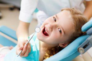 child smiling sitting dentist chair