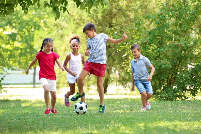 Group of children playing soccer outside