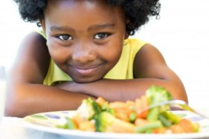 little girl smiling with plate of vegetables
