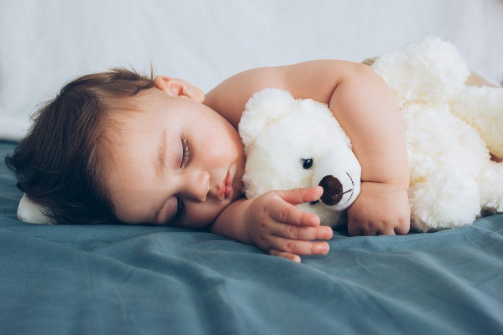 Closeup of baby sleeping on bed with stuffed animal