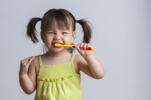 Girl brushing her teeth with fluoride for kids